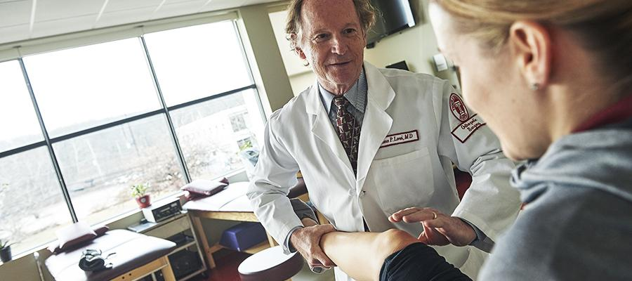 Orthopaedic physician testing knee movement