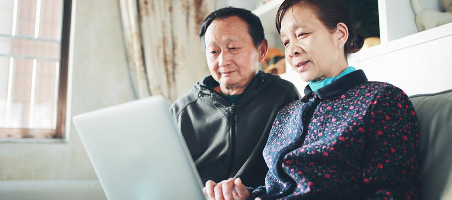 Senior couple using laptop on couch