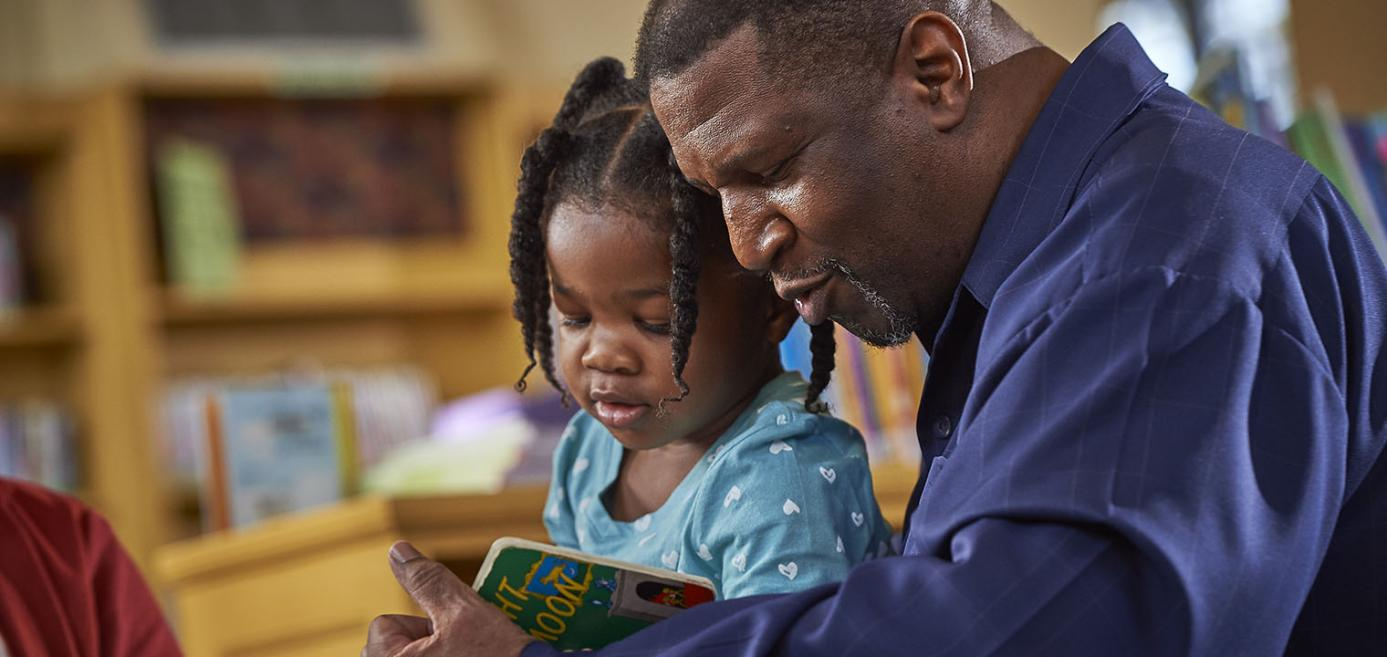Man and daughter reading a book together