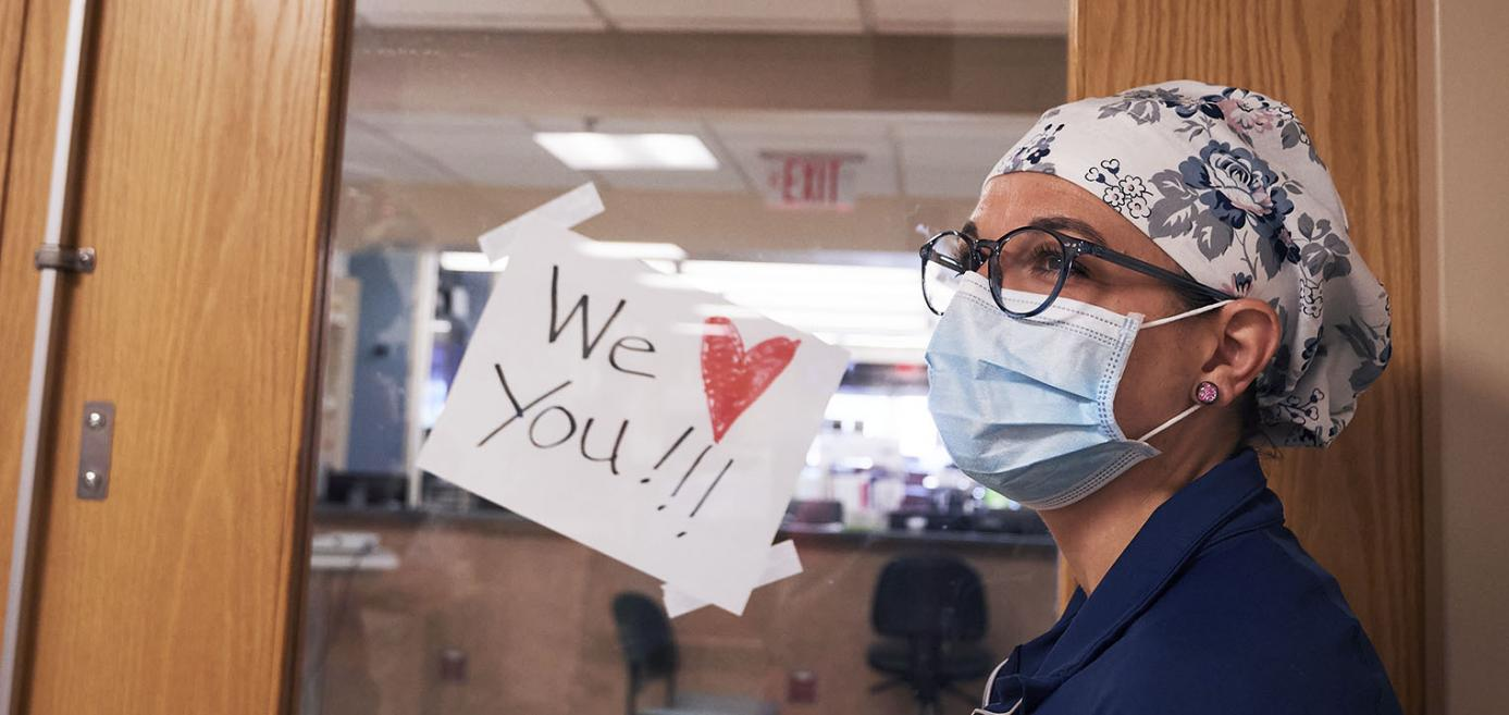 "Doctor standing next to ""We Love You"" sign"