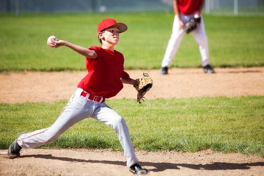 Little League baseball player pitching at game