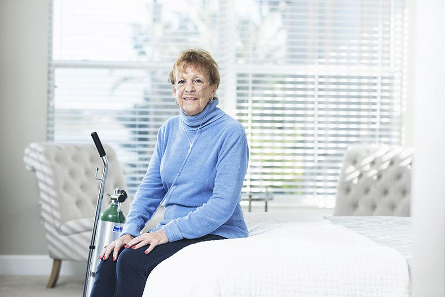 Woman sitting on bed with her oxygen equipment