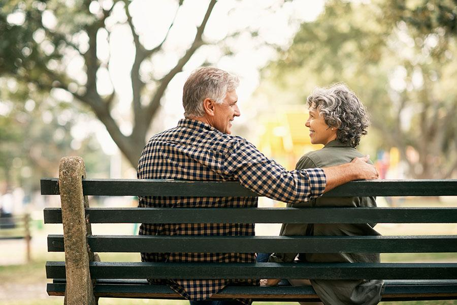 Happy senior couple relaxing on a park bench