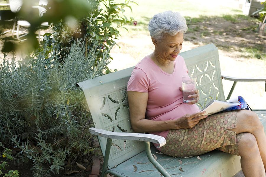 Older woman reading a magazine with a glass of water outside