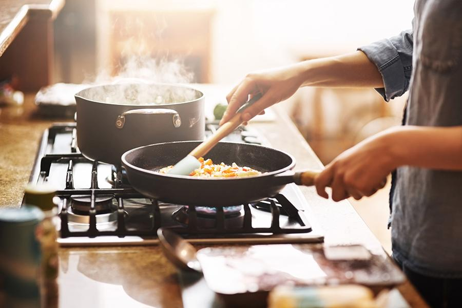 Woman cooking healthy recipe on stove