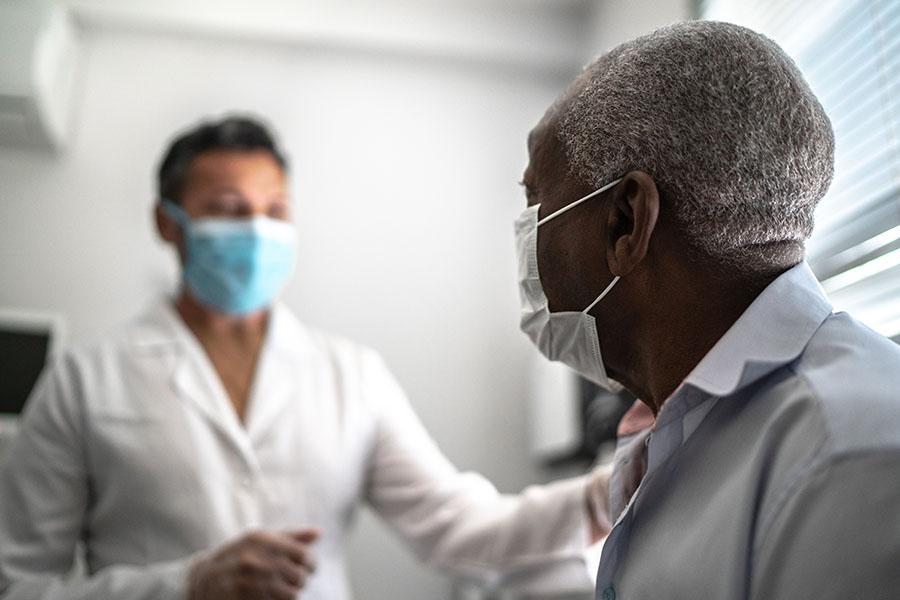 Doctor talking with patient at appointment while both wear masks