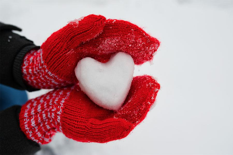 Heart-shaped snowball in gloved hand