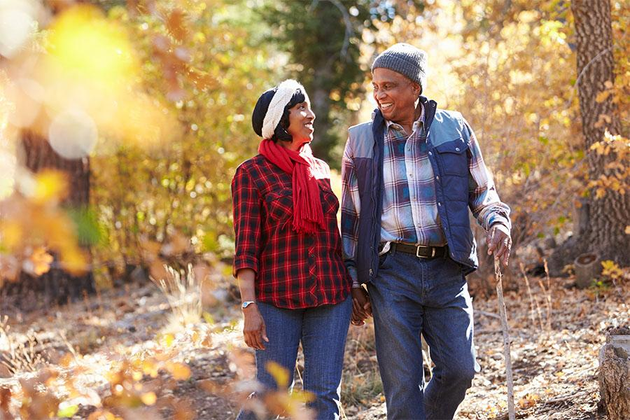 Senior African American couple walking through woods