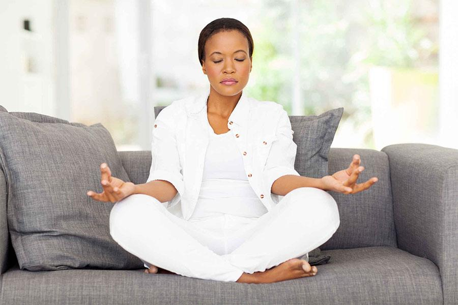 Woman sitting on the couch meditating