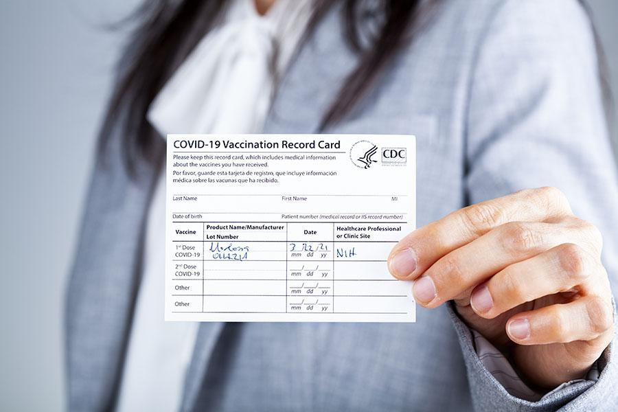 Woman holding Covid-19 vaccine card