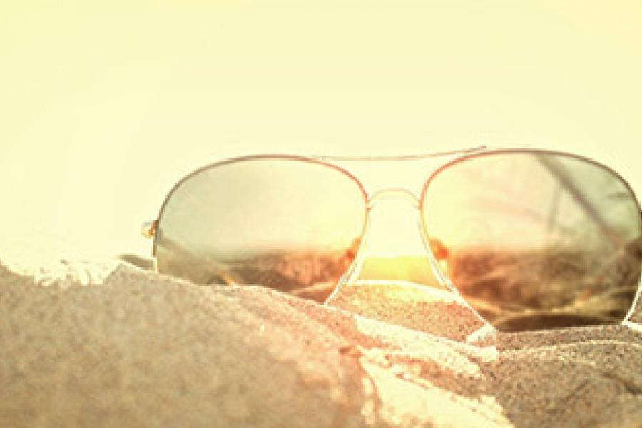 Pair of sunglasses laying on top of sand