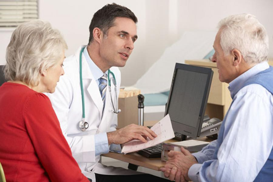 Temple physician explaining results to elder couple