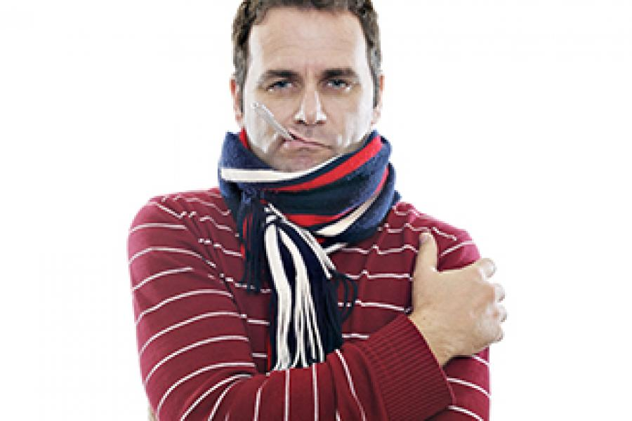 Man wrapped up in a scarf with a thermometer hanging out of his mouth