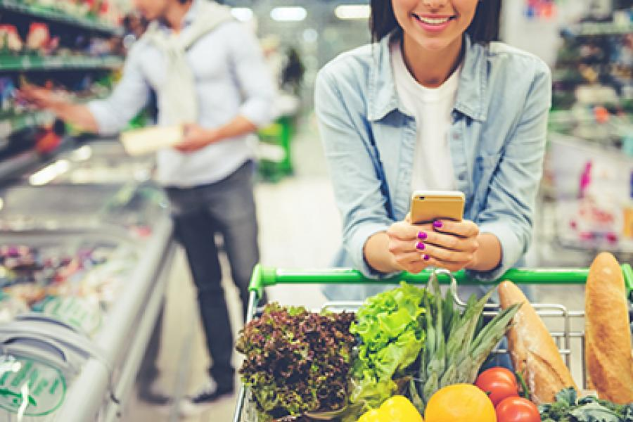 Closeup of woman pushing grocery cart while looking at her phone