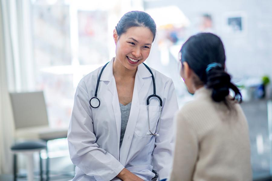 Physician smiling and talking to patient
