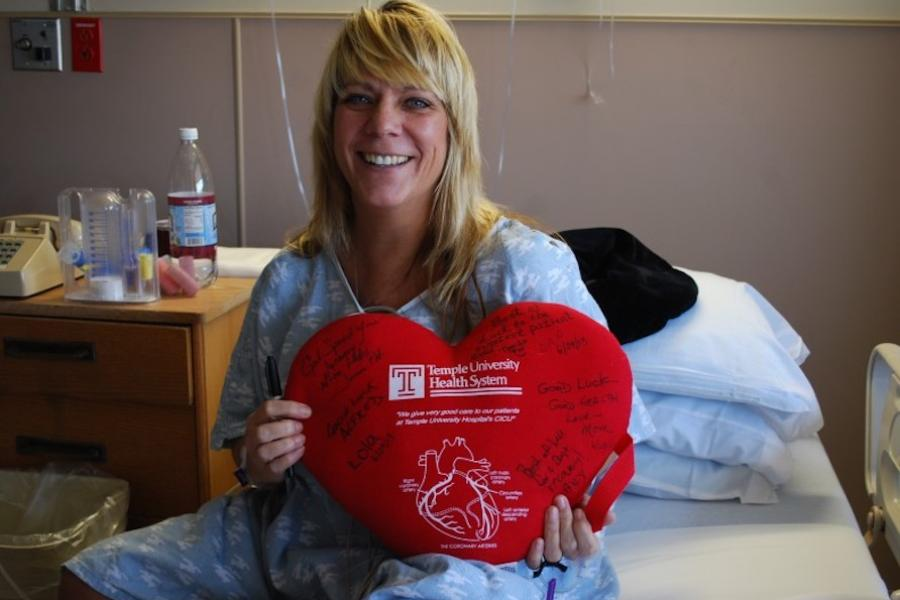 Temple patient, Heather, in her hospital bed with a heart shaped Temple pillow