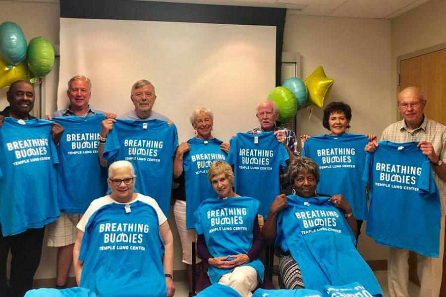 Breathing buddies group holding T-shirts