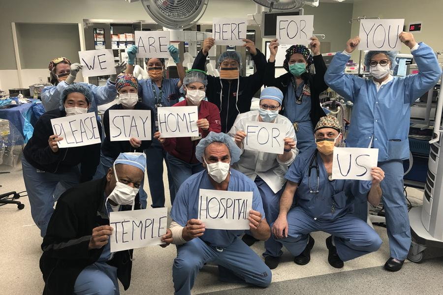 "Temple University hospital staff holding signs that say ""We are here for you please stay at home for us"""