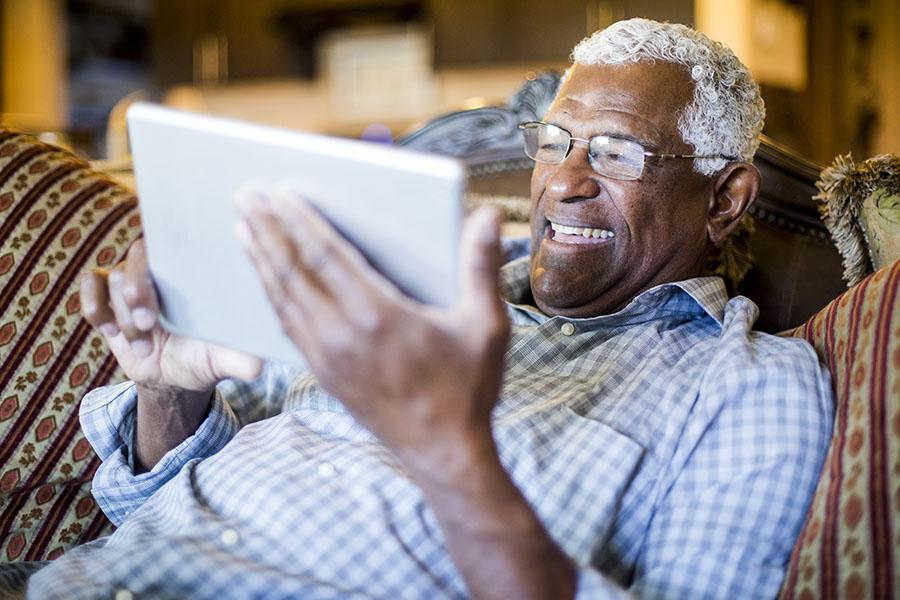 Elderly man on a couch with a tablet