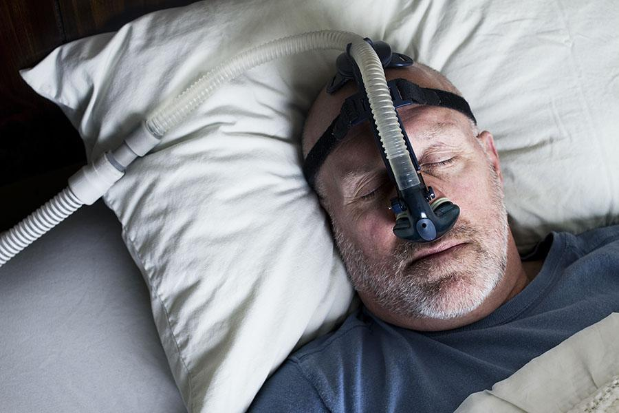 Man sleeping in bed using CPAP machine
