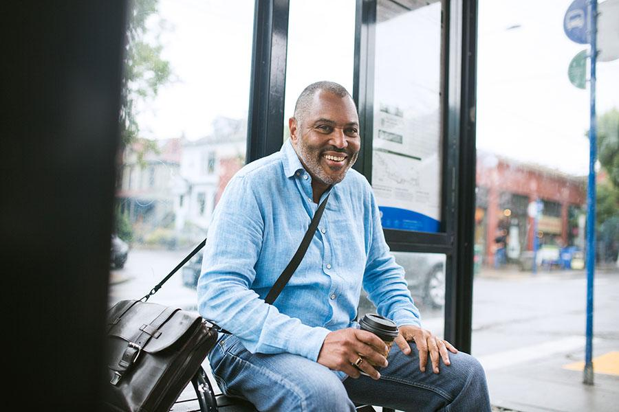 Man smiling waiting for bus