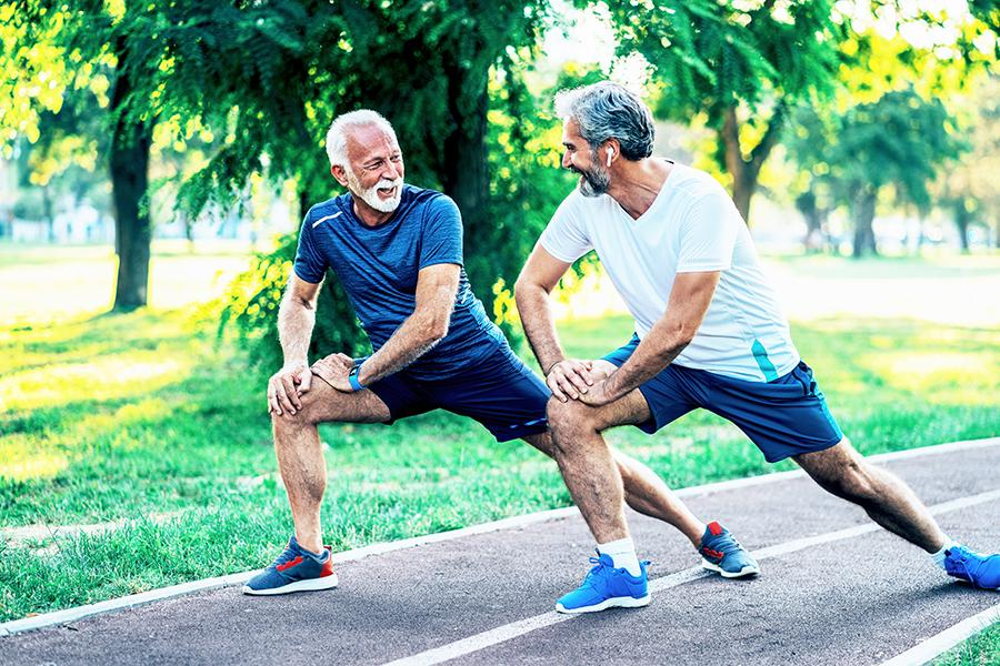 Two men stretching and talking before going for a run outside