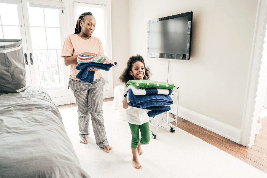 Mother and daughter walking with folded laundry around the house