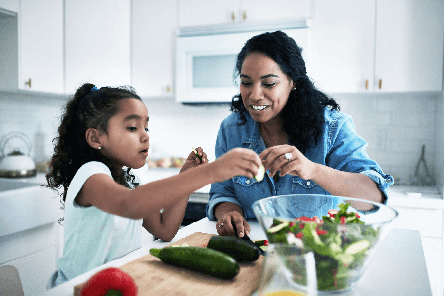 Mother and daughter cooking healthy recipe together