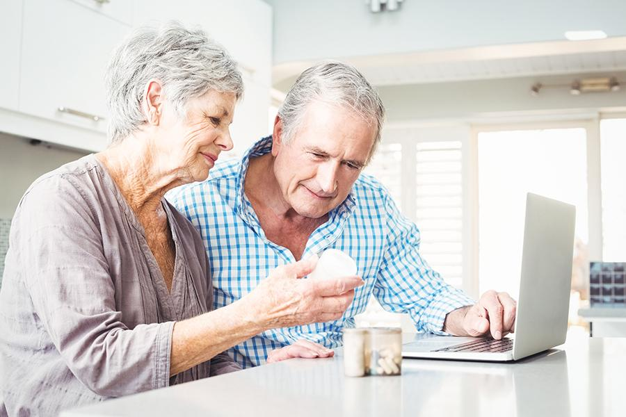 Older couple going over medications together at kitchen counter