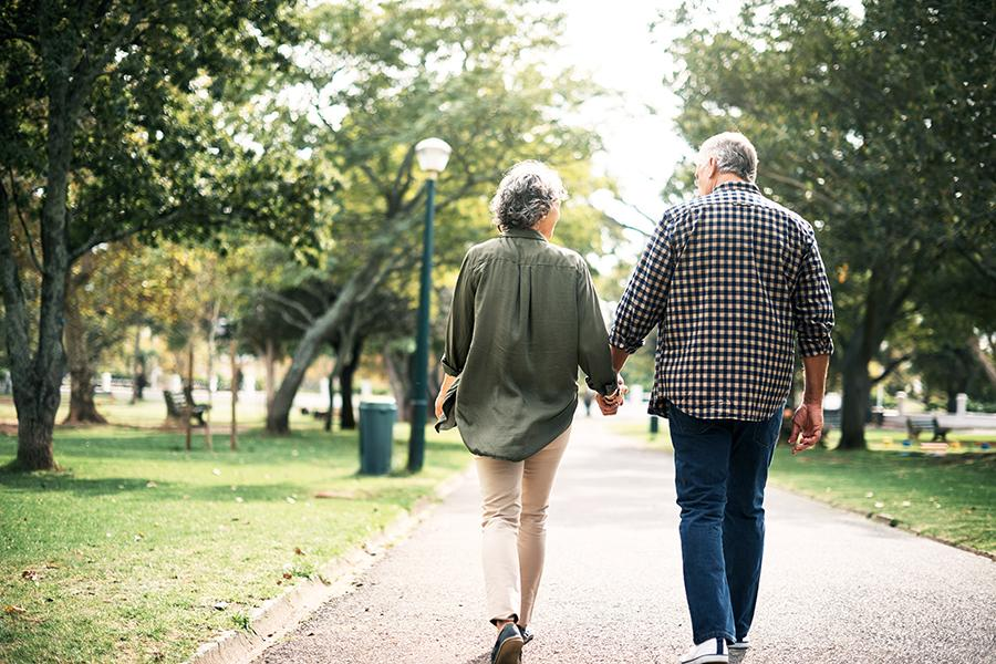 Older couple holding hands and walking outside