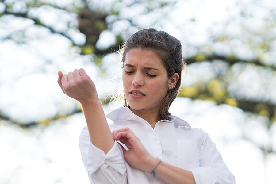 Woman itching dry skin outside