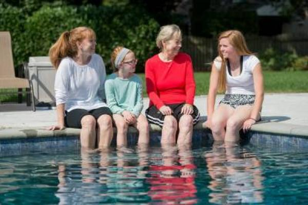 Temple patient Betsy and her family sitting with their feet in the pool