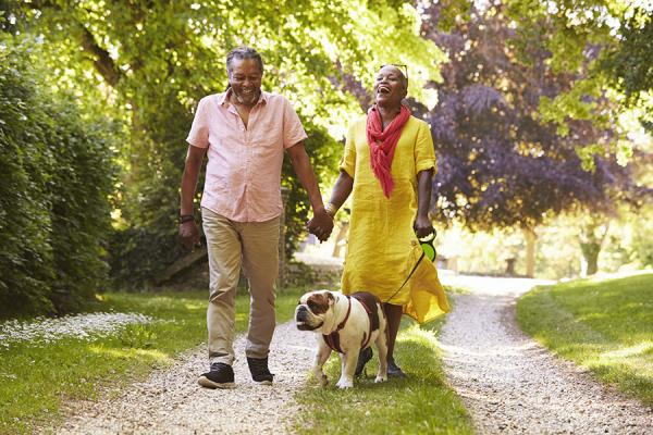 Couple holding hands and walking dog