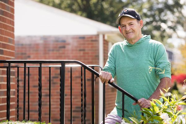Kidney transplant patient, George P., holding stair railing outside