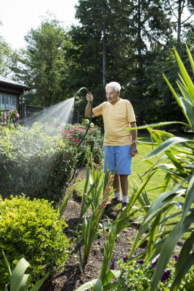 Jeanes patient, Albert, watering flowers in his garden