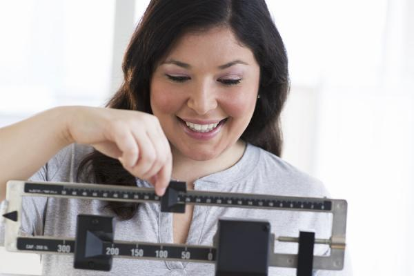 Bariatric surgery patient weighing herself on scale