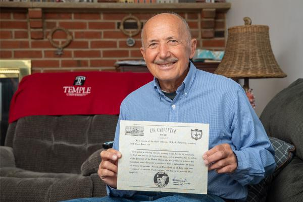 Heart transplant patient Heinz holding his USS Carpenter certificate