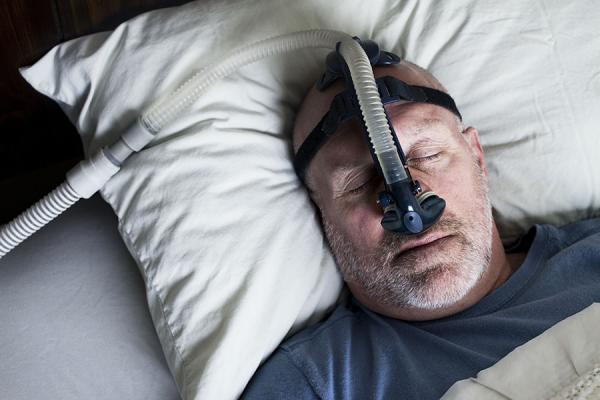 Man sleeping in bed using CPAP machine