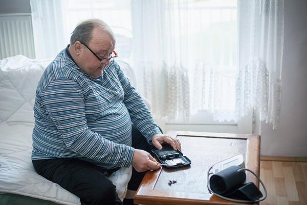 Older man checking blood sugar levels